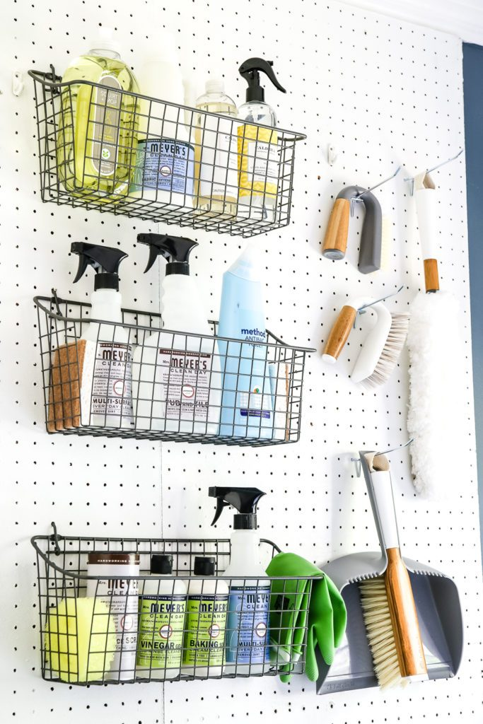 A few peg hooks for holding scrub brushes and dust pans and these pegboard baskets for storing bottles of cleaning supplies do a world of good.